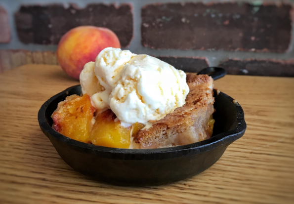 Enjoy peak peach season with this gluten free peach cobbler recipe from Jewel's Bakery and Cafe! 2geekswhoeat.com #glutenfree #baking